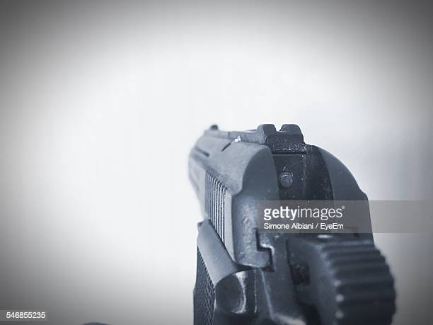 Close-Up Of Handgun Pointing Against White Background