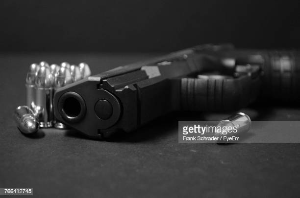 close-up of handgun with bullets on table - frank schrader stock pictures, royalty-free photos & images