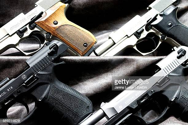 close-up of handguns on fabric - armi foto e immagini stock