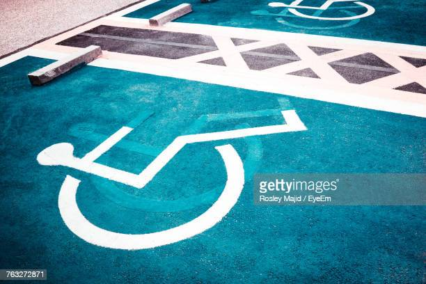 close-up of handicapped sign on blue road - disabled sign stock photos and pictures