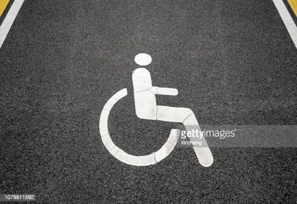 close-up of handicapped sign on road - disabled sign stock photos and pictures