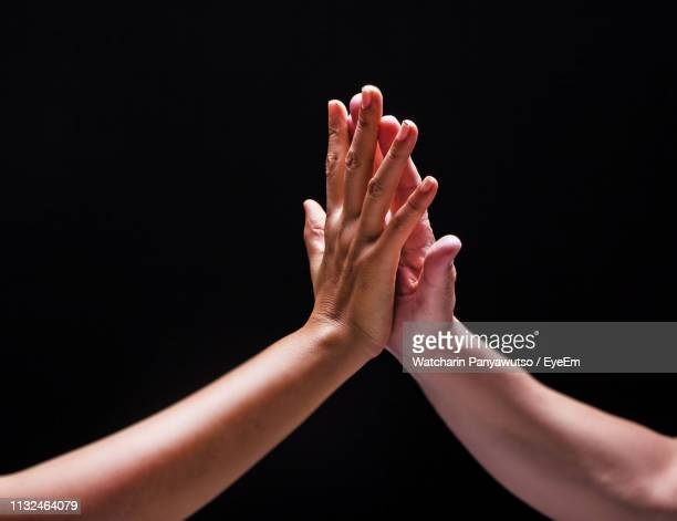 close-up of hands against black background - high five stock-fotos und bilder