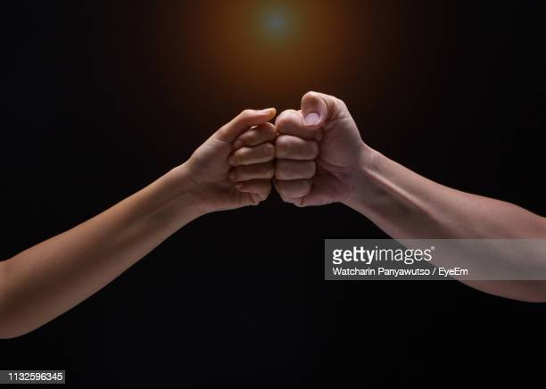 close-up of hands against black background - fist bump stock pictures, royalty-free photos & images