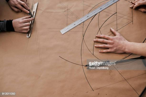 closeup of hands and rulers on paper - robin skjoldborg stock pictures, royalty-free photos & images