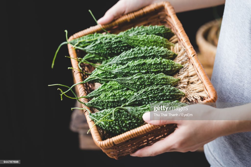 Close-Up Of Hands Carrying Bitter Gourds In Wicker Tray : Stock Photo