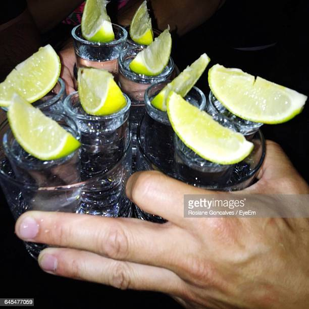 Close-Up Of Hands Carrying Tequila Shots