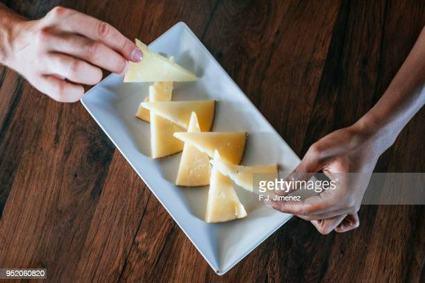close-up of hands catching cheese from a dish - queijo imagens e fotografias de stock