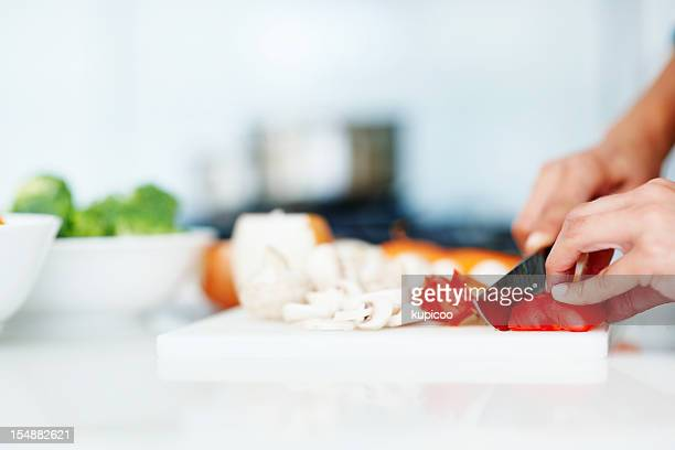 Closeup of hands chopping vegetables in the kitchen