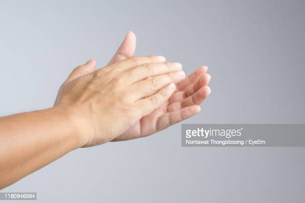 close-up of hands clapping against gray background - applauding stock pictures, royalty-free photos & images
