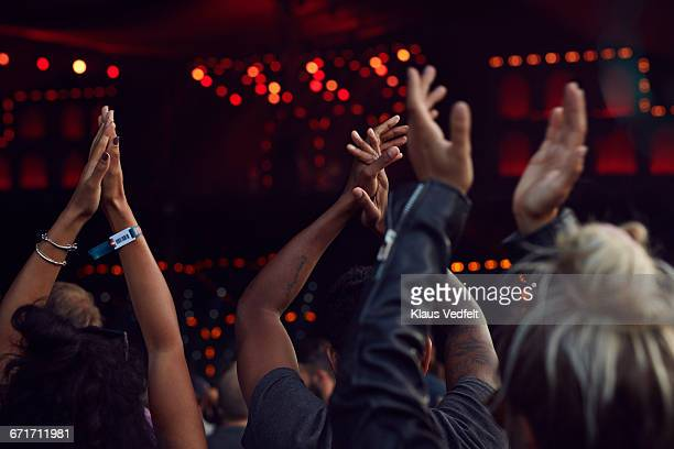 Close-up of hands clapping at concert