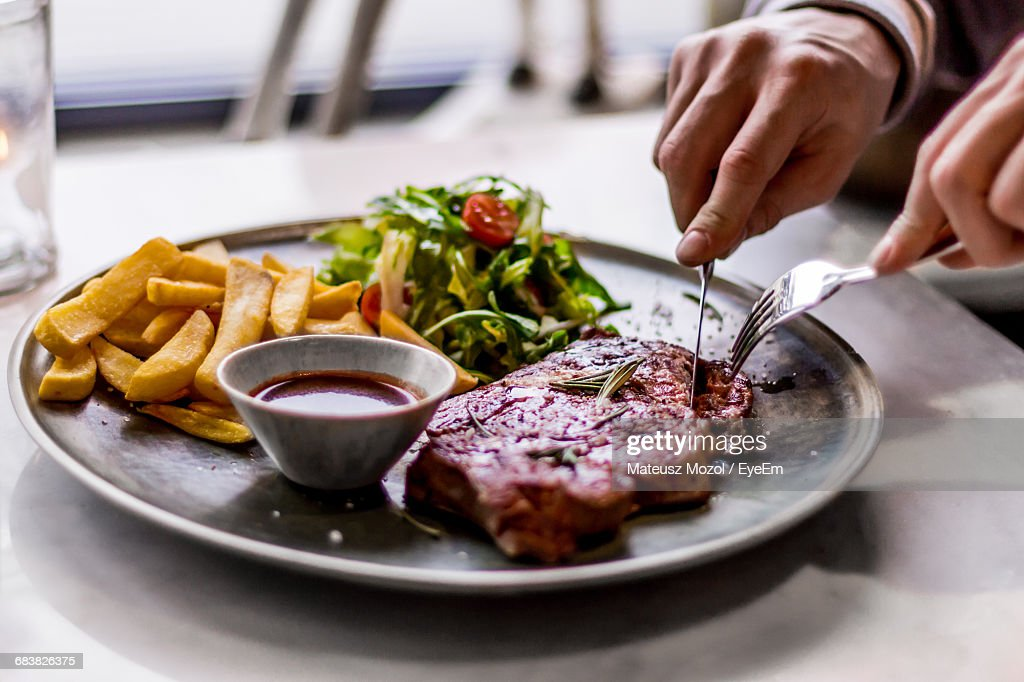 Close-Up Of Hands Cutting Into Steak Served On Plate With Fries : Stock Photo