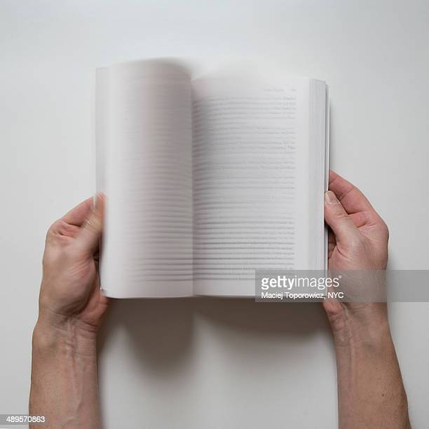 Close-up of hands fanning a book.