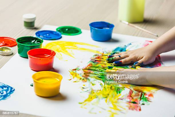 close-up of hands finger painting on drawing paper - finger painting stock pictures, royalty-free photos & images