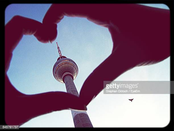 Close-Up Of Hands Forming Heart Shape Against Tower