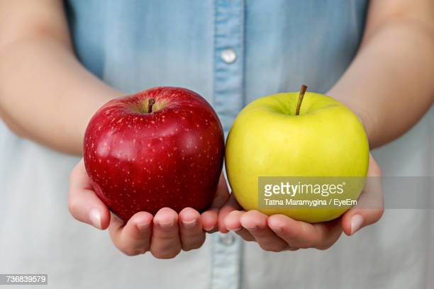 close-up of hands holding apples - dois objetos - fotografias e filmes do acervo