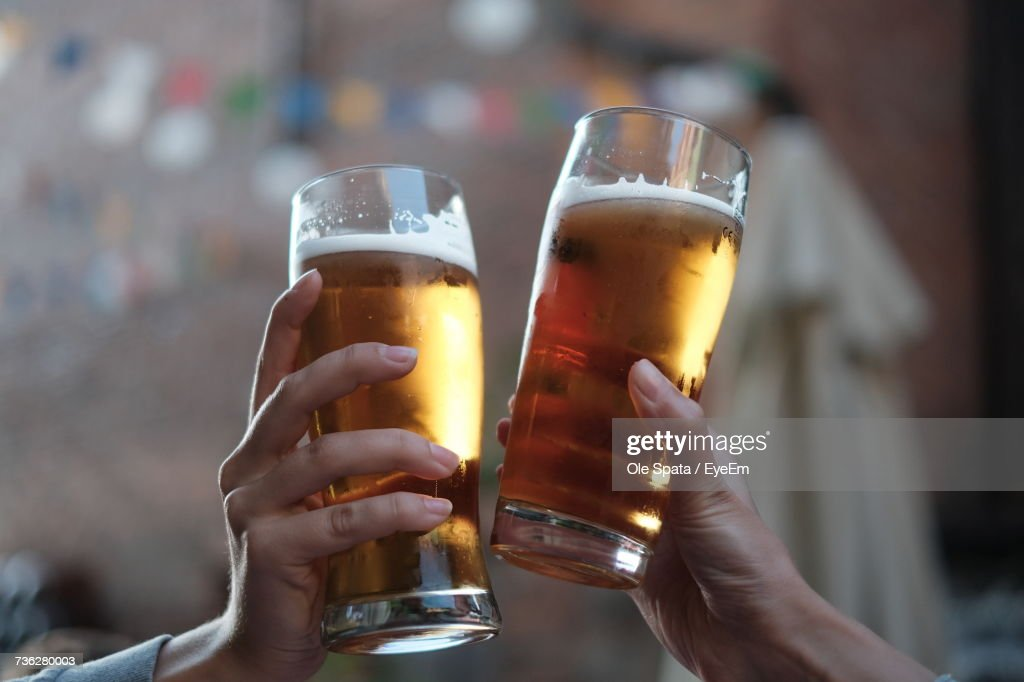 Close-Up Of Hands Holding Beer Glasses : Stock Photo