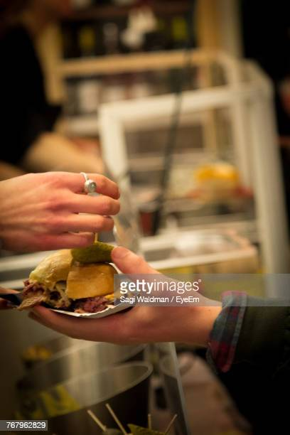 Close-Up Of Hands Holding Burger