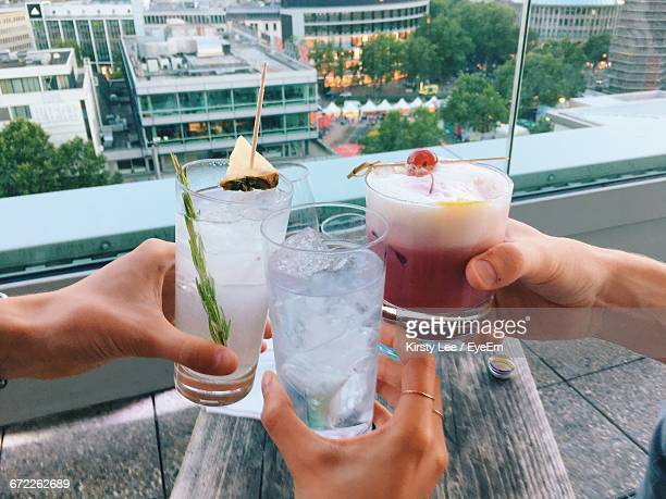 Close-Up Of Hands Holding Cocktail Drinks