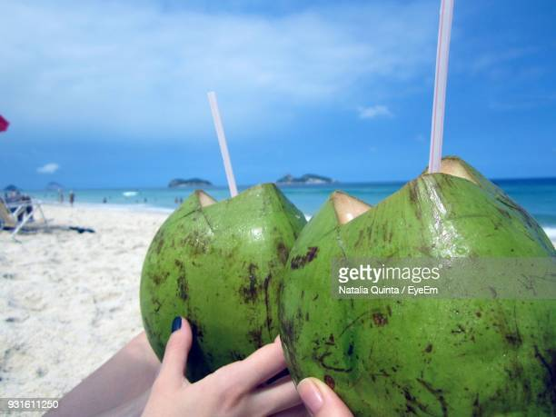 close-up of hands holding coconuts at beach against sky - coconut water stock pictures, royalty-free photos & images