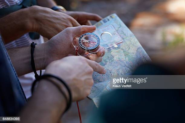 close-up of hands holding compass & map - compass stock pictures, royalty-free photos & images