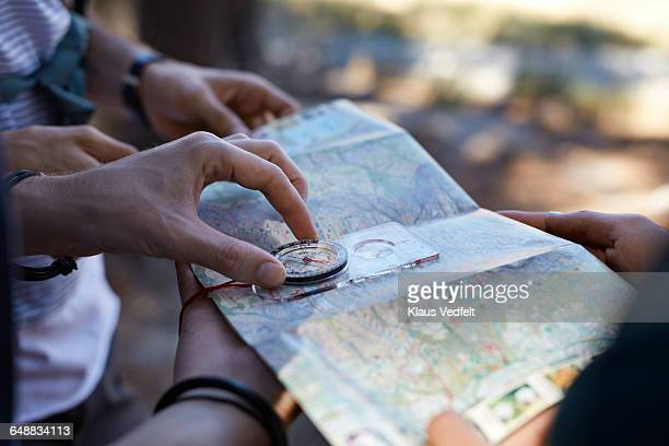 close-up of hands holding compass & map - karte navigationsinstrument stock-fotos und bilder