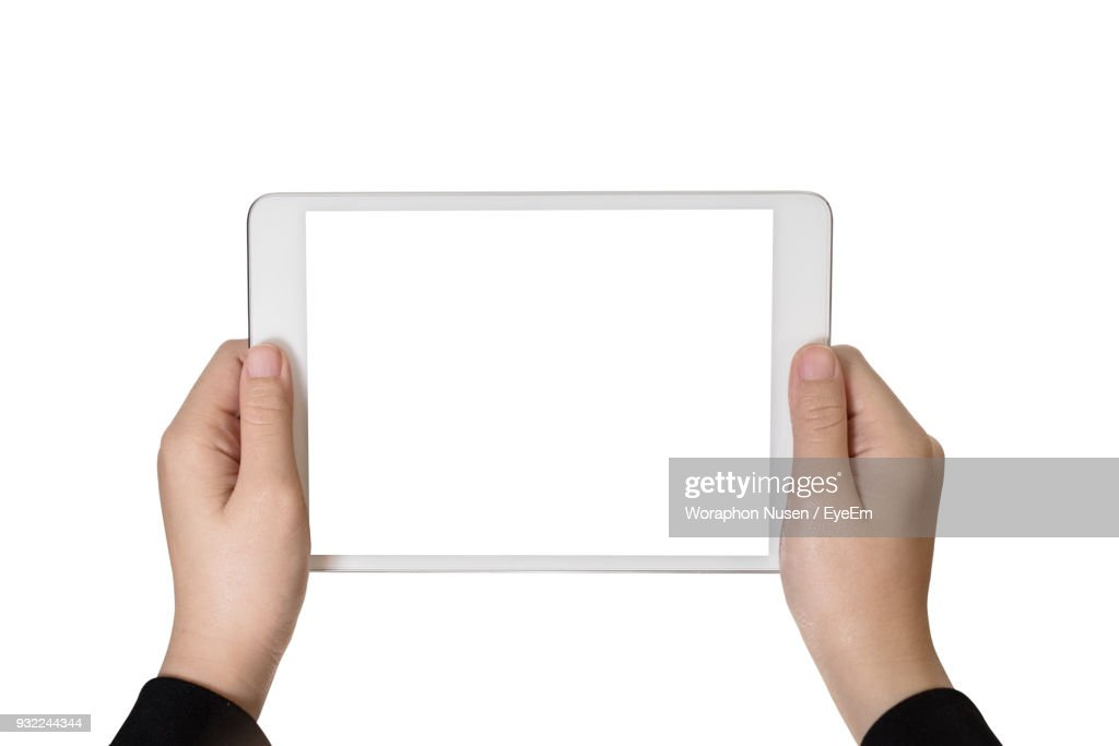 Close-Up Of Hands Holding Digital Tablet Over White Background : Stock Photo