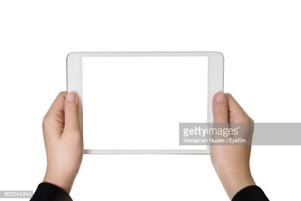 close-up of hands holding digital tablet over white background - menschliche hand stock-fotos und bilder