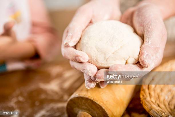 Close-up of hands holding dough