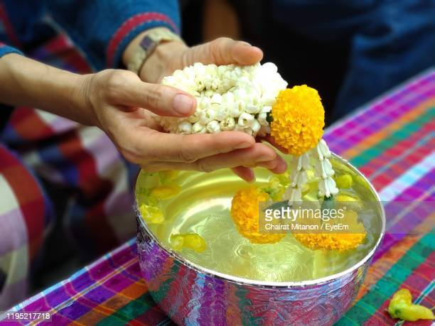 close-up of hands holding flowers - buddhist new year stock pictures, royalty-free photos & images