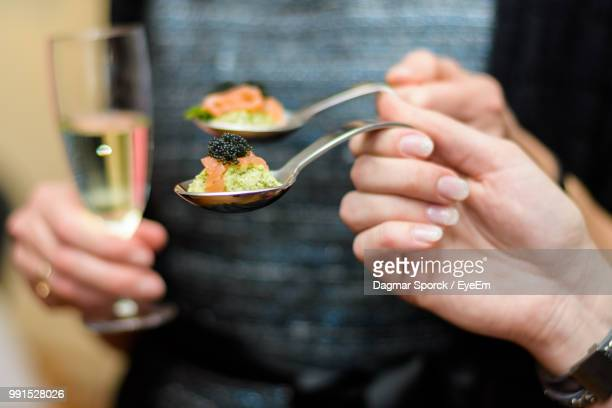 Close-Up Of Hands Holding Food And Drink