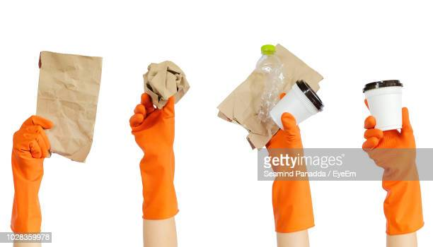 Close-Up Of Hands Holding Garbage Over White Background