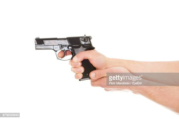 Close-Up Of Hands Holding Gun Over White Background