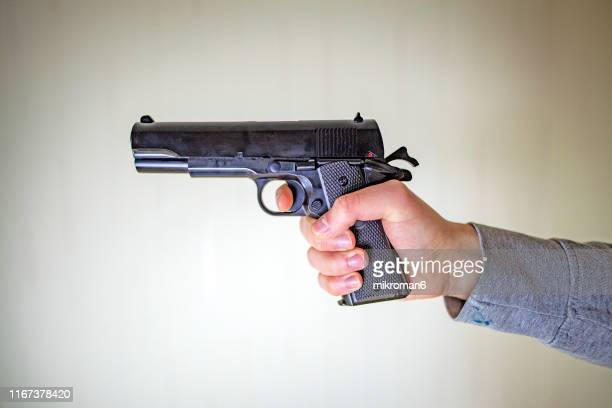 close-up of hands holding gun - handgun stock pictures, royalty-free photos & images
