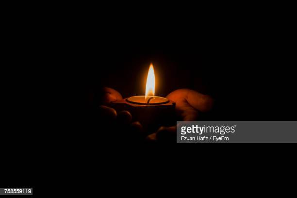 close-up of hands holding illuminated candle in darkroom - diya oil lamp stock pictures, royalty-free photos & images