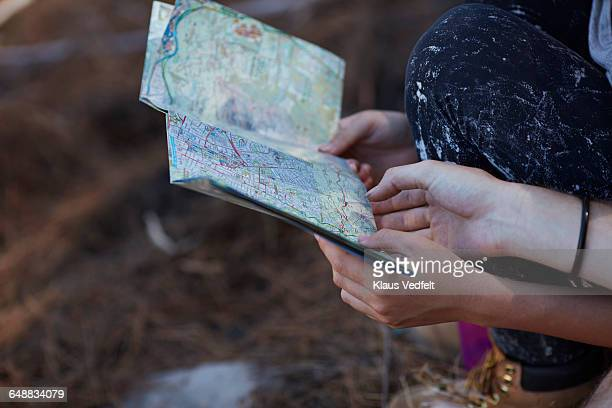 Close-up of hands holding map in forrest