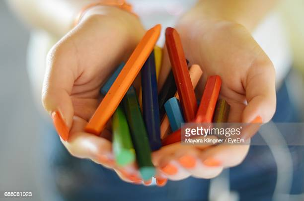 Close-Up Of Hands Holding Multi Colored Crayons