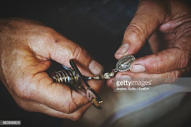 Close-Up Of Hands Holding Pendant And Multi Purpose Tool