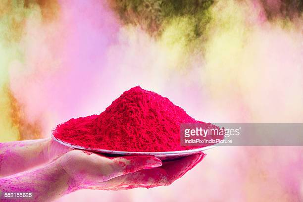 Close-up of hands holding plate with pink color gulal during Holi festival