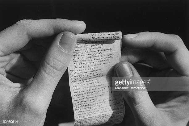 Closeup of hands holding poems written on cigarette papers by Irina Ratushinskaya Russian emigre poet human rights activist who wrote these poems...