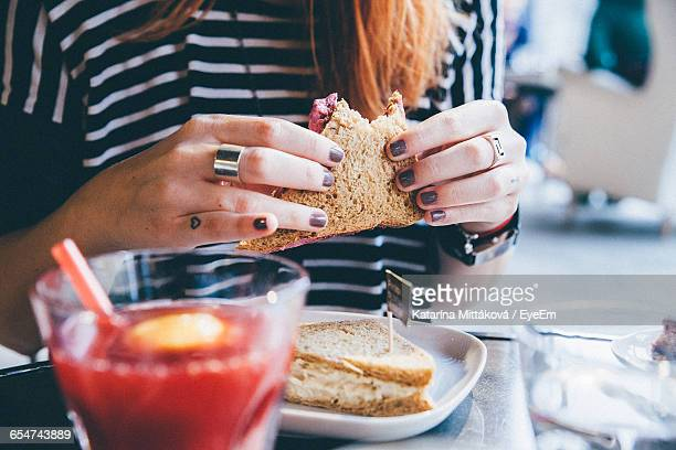 Close-Up Of Hands Holding Sandwich