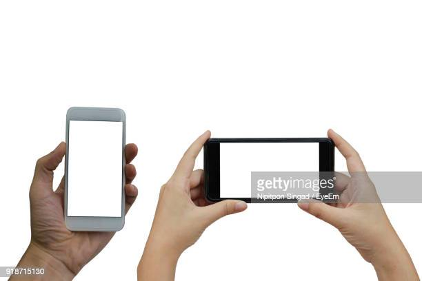 Close-Up Of Hands Holding Smart Phone Against White Background