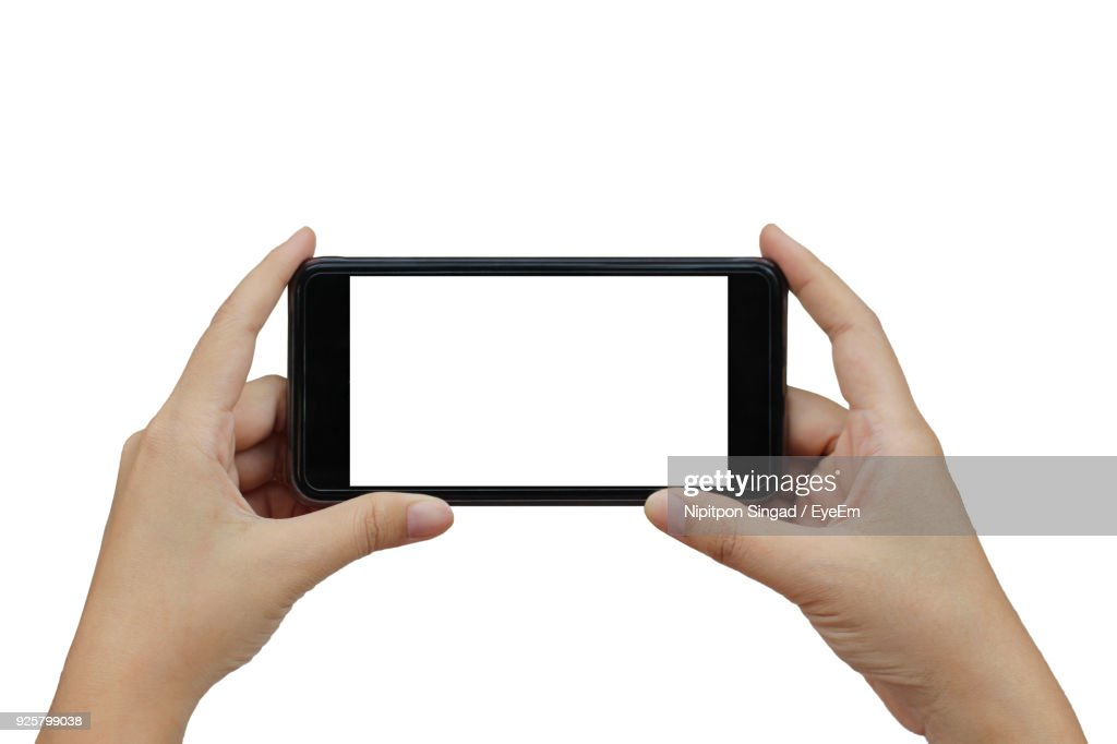 Close-Up Of Hands Holding Smart Phone Against White Background : Stock Photo