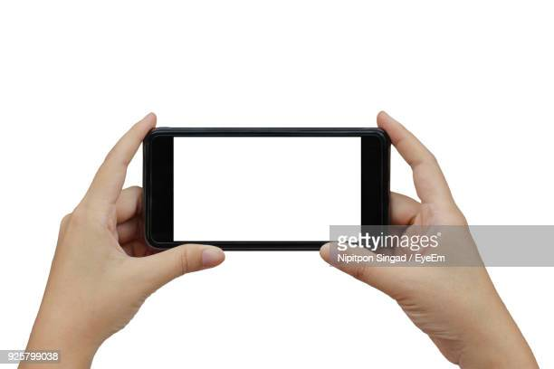 close-up of hands holding smart phone against white background - menschliche hand stock-fotos und bilder