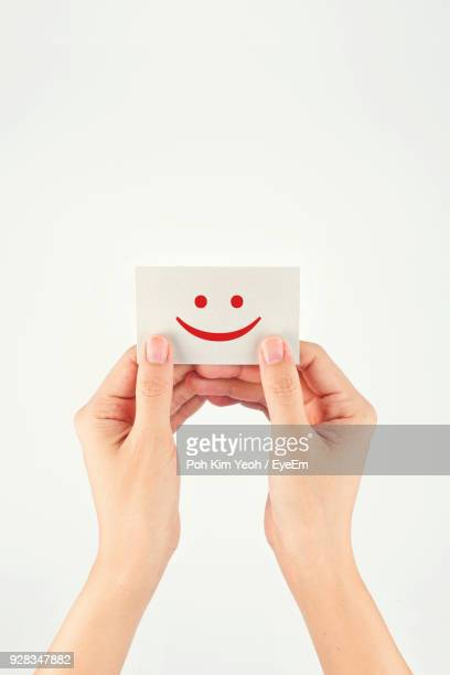Close-Up Of Hands Holding Smiley Face On Paper Against White Background