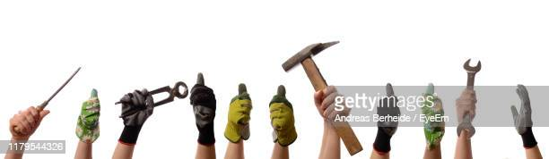close-up of hands holding tools against white background - work glove stock pictures, royalty-free photos & images