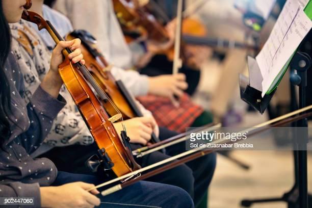Close-up of hands holding violins