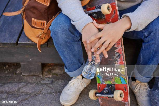 closeup of hands holding water bottle and skateboard - robin skjoldborg stock pictures, royalty-free photos & images