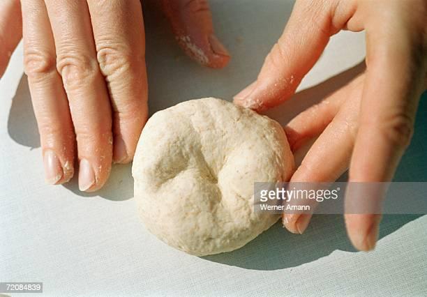 Close-up of hands kneading dough