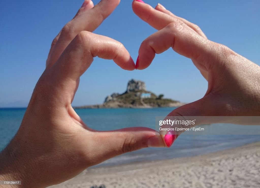 Close-Up Of Hands Making Heart Shape Against Clear Sky : Photo