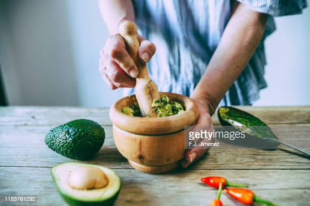 close-up of hands making homemade guacamole - guacamole stock photos and pictures